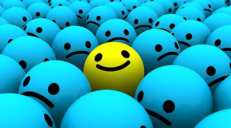 be different be happy yellow smiley in middle of sad blue smileys
