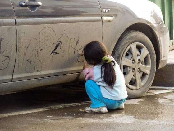Little Girl Drawing On A Dirty Car