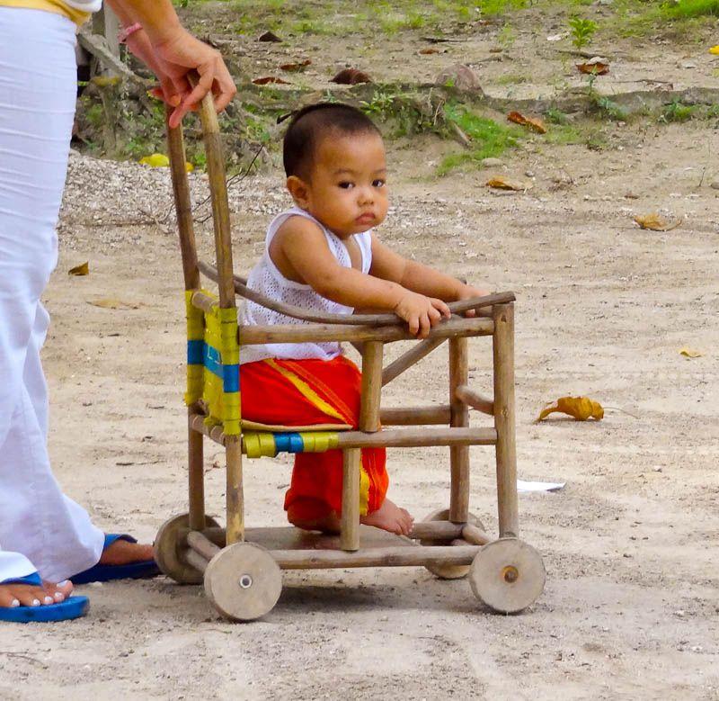 little boy in wooden stroller