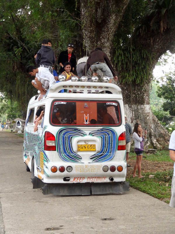 people riding on the roof of a bus