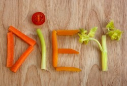 The word diet spelled out in vegetables on a wooden board.