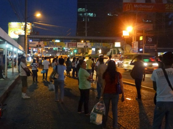People Waiting For Jeepneys On The Side Of The Road